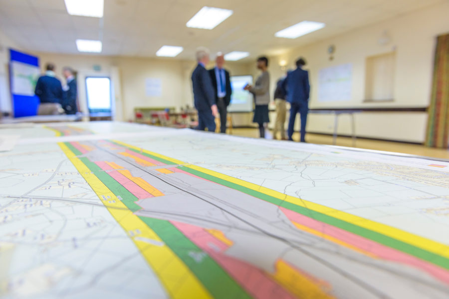 a long map on the table in the foreground with a group of standing people behind talking.