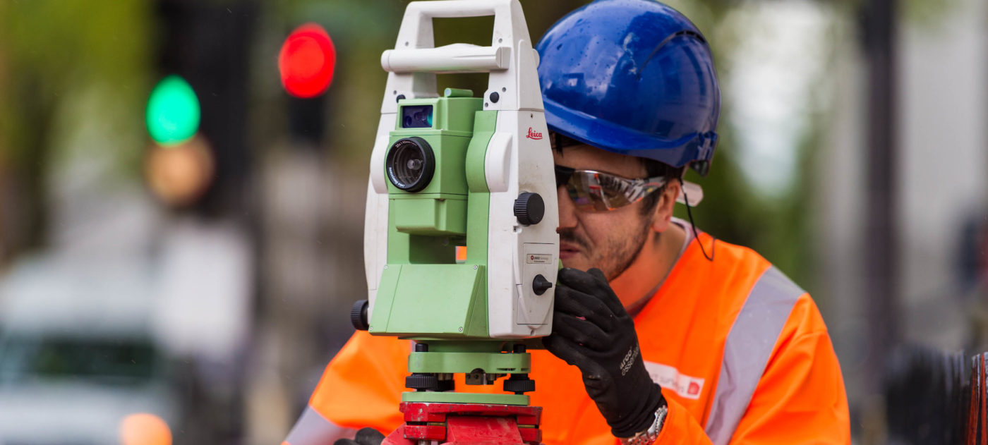 Man in blue hard hat and orange PPE using a laser measurement tool.