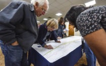 members of the public lean on a table with a map on it.