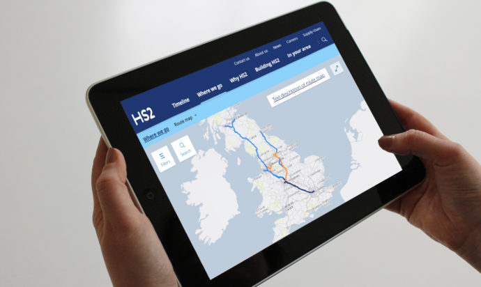 Hands holding a tablet displaying a map of the HS2 route