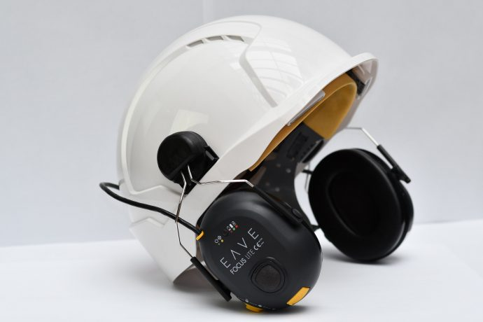 Construction hard hat with ear defenders attached to side.