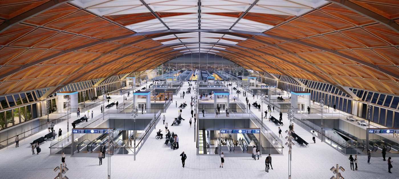 CGI image of the interior of a station under a large roof arch with a concourse below.