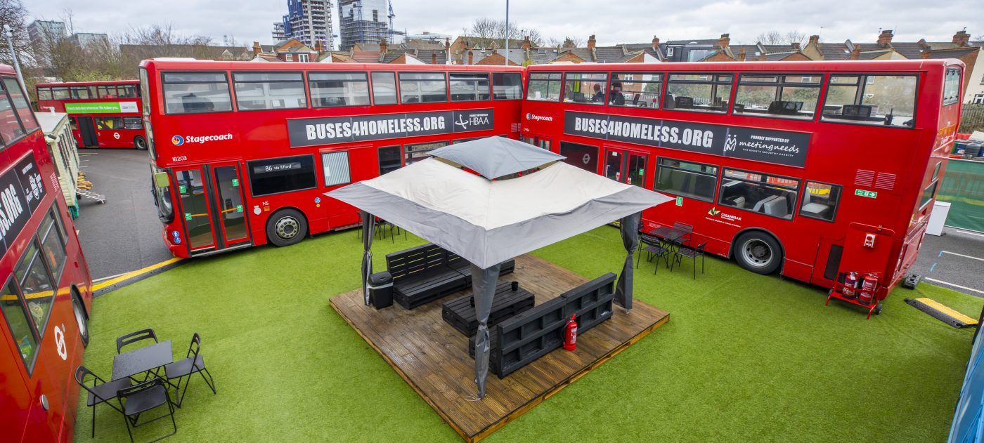 Converted double deck buses provide emergency shelter for homeless people, parked around a sitting area.