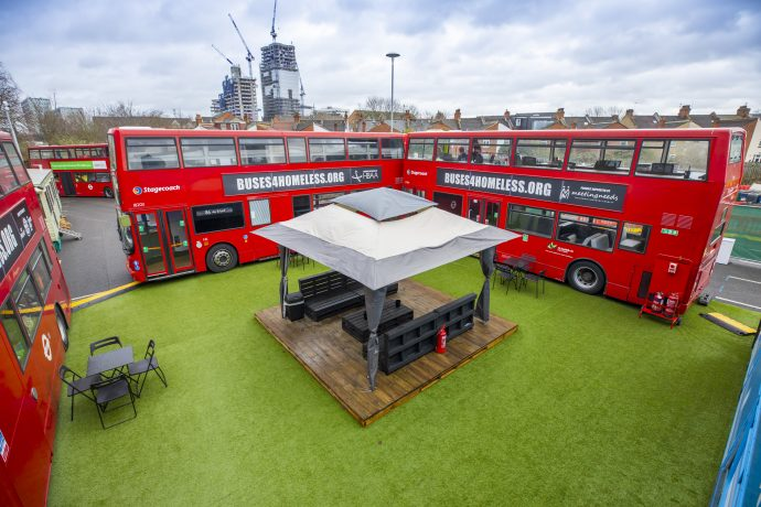 Converted buses parked in a square offering space for homeless people to live and train.