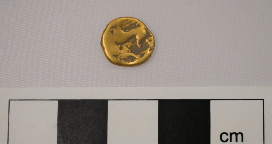 A gold coin, uninscribed, next to an ruler showing its size as about 1cm.