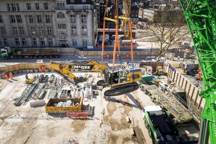 The view from a tower crane's cab down over a construction site as the crane lifts an excavator across the site.