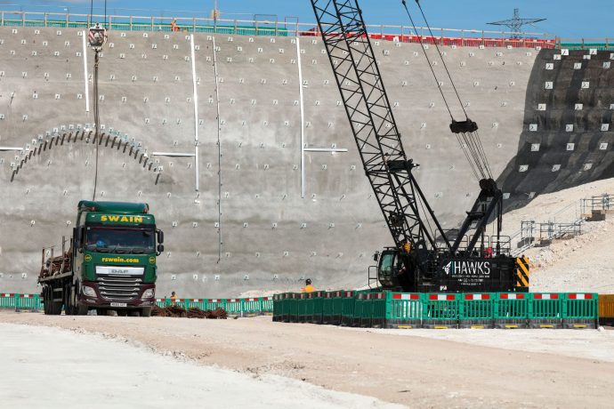 Crane unloading a lorry next to the head wall of a cutting.