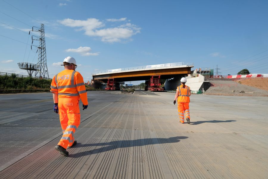 Construction workers view the move of a large bridge into place over a motorway. It will provide improved access to Interchange station.