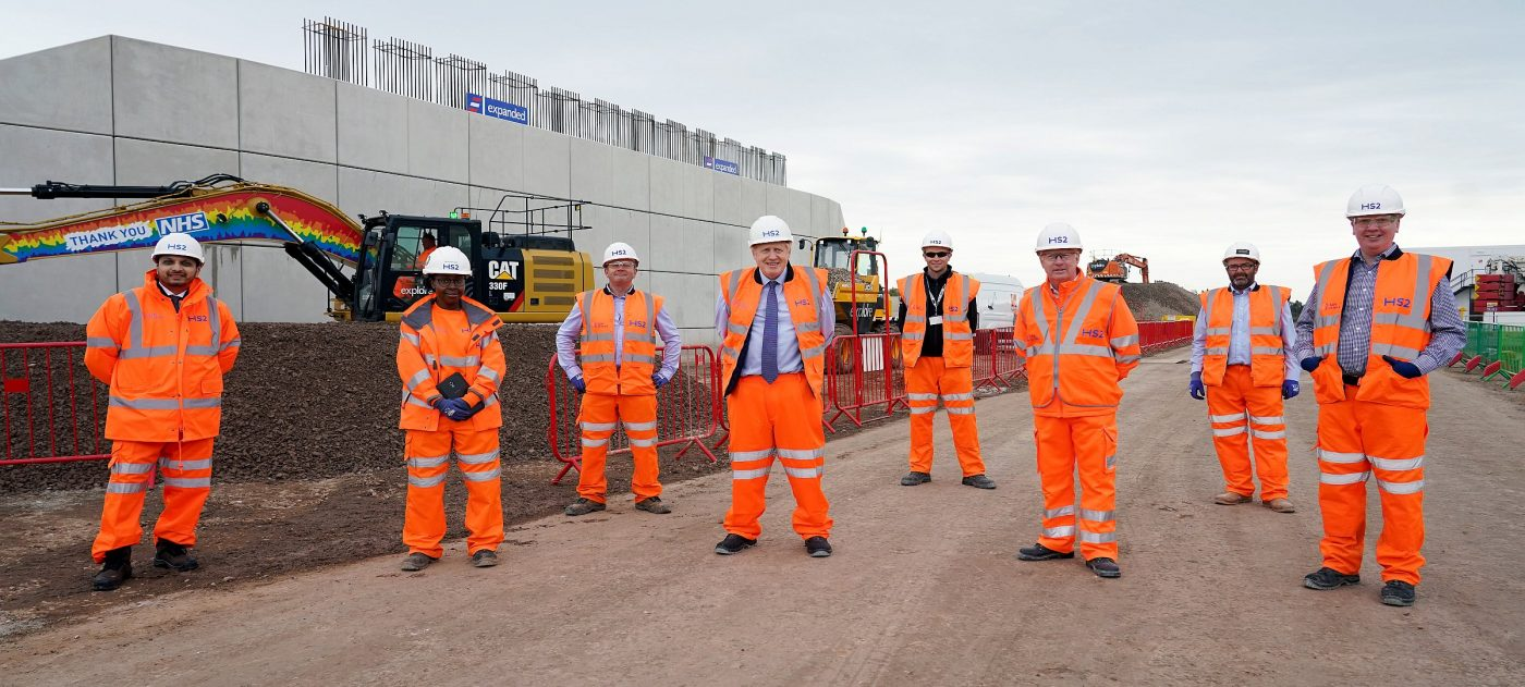 Prime Minister Boris Johnson stands with HS2 workes between two bridge abutments on a construction site.