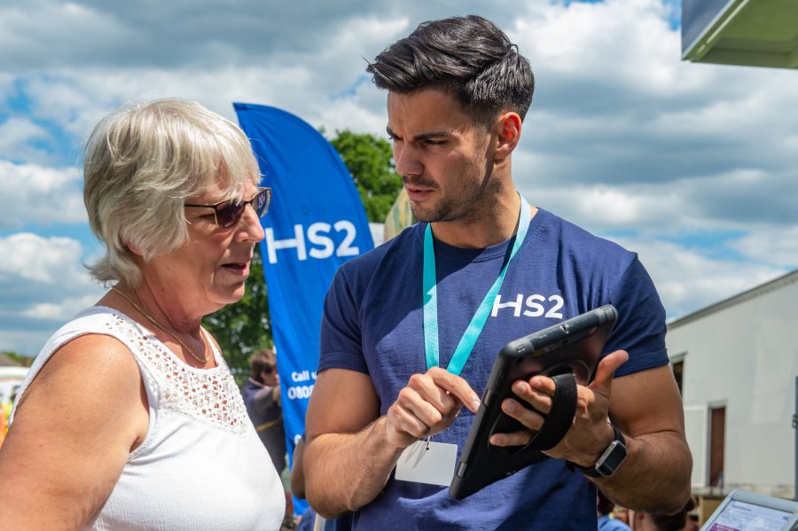 Lady with white vest and grey hair is shown something on an iPad by HS2 worker