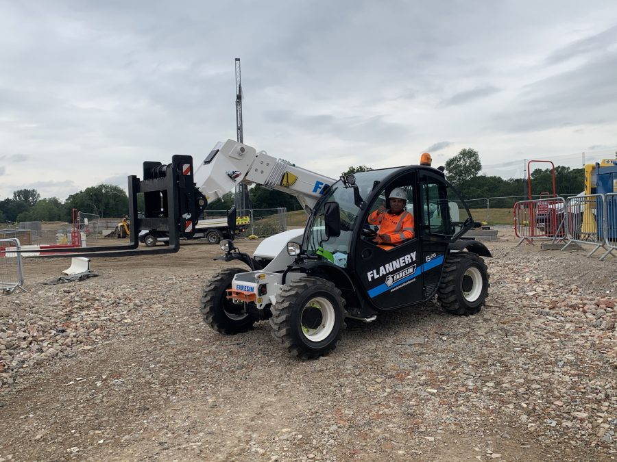 An electric powered telehandler on a construction site.