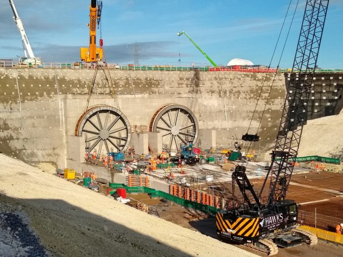 Circular steel tunnel seals are lowered into position against the head wall of a tunnel cutting.