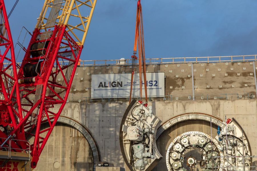 Two large circular steel seal structures are lowered into place against the headwall of a tunnel cutting.