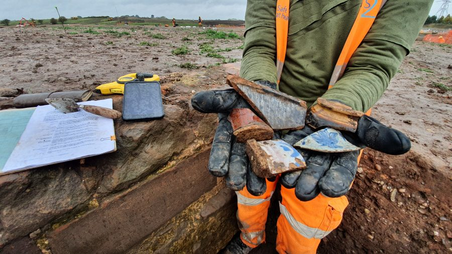 A Wessex Archaeologist presents some post medieval pottery sherds from the site of Coleshill Medieval Manor. In the photo can be seen a digital recording tablet, a trowel and an archaeologists tools.