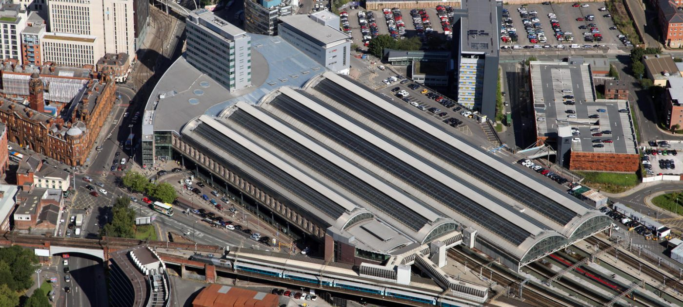 Aerial view of Manchester Piccadilly station showing its roof and surrounding buildings.