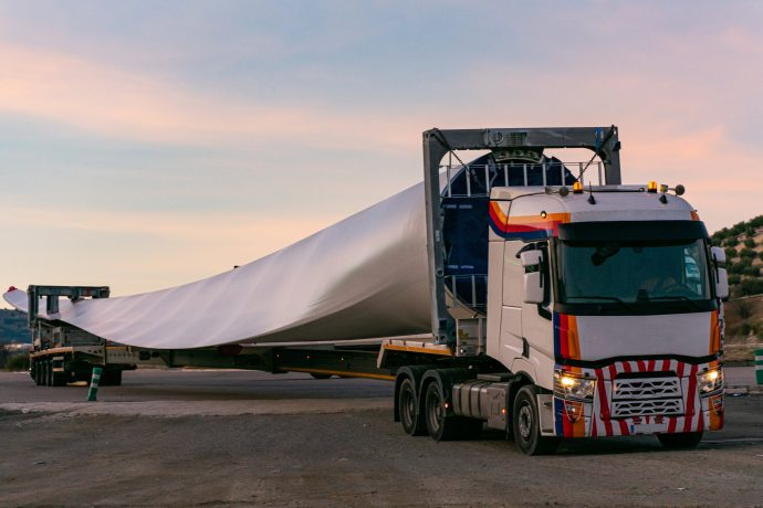 A wind turbine blade is pulled by a lorry.