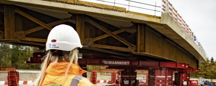 Woman facing away from camera with white hard hat on and orange PPE looking over a bridge being moved