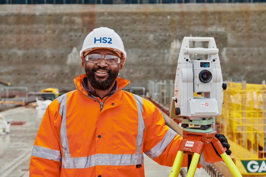 A HS2 worker stands on a construction site wearing protective clothing and headwear. He is next to a surveying instrument on a tripod stand.