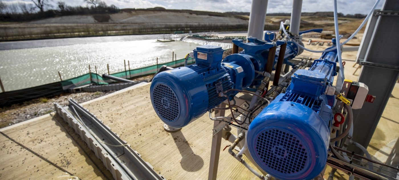 Two industrial water pumps sit on a structure next to a settling pond.