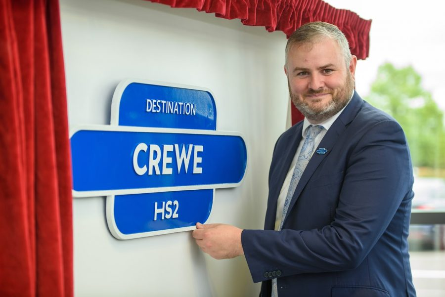 A person stands next to a blue station plaque that says 'Destination Crewe HS2'. Around it are open curtains.